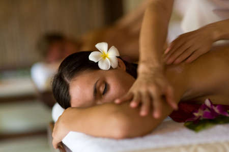 A young woman having massage in tropical spa Stock Photo