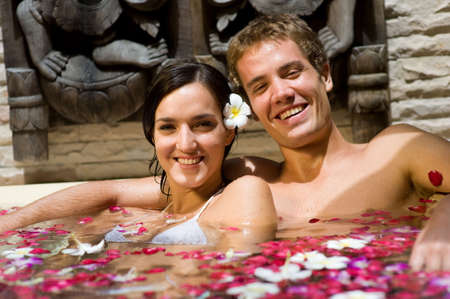 bathing man: A young couple together in a bath with petals and flowers at a tropical spa Stock Photo