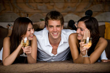 affluent: Three attractive young adults lying together in smart clothing