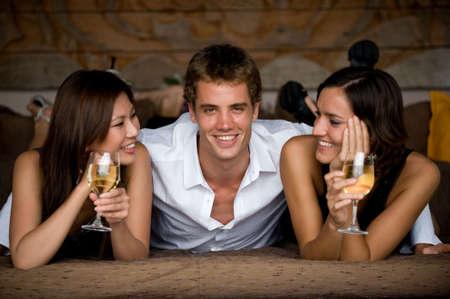 trio: Tres adultos j�venes atractivos que mienten junto en la ropa elegante