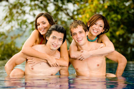 Four friends having fun in pool on vacation photo