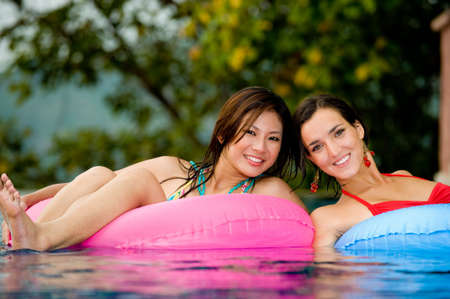 Two young women in inflatables in the pool photo