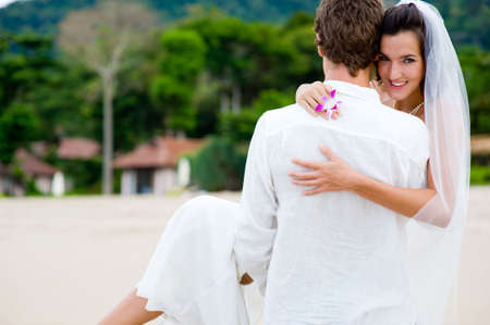 A young couple just married on a tropical beach photo