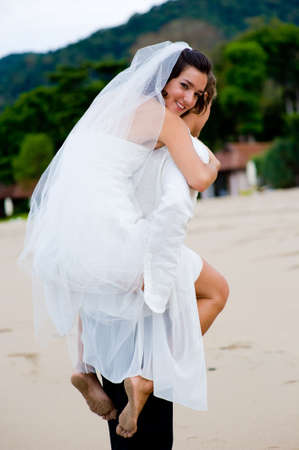 A young couple just married on a tropical beach Stock Photo