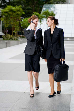 blouse: Two businesswomen walking together outside Stock Photo