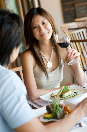 outdoor restaurant: A young woman smiling whilst eating dinner at a restaurant