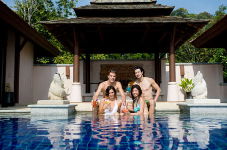 orchid house: Four young adults sitting in a pool with tropical cocktails Stock Photo