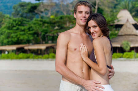 A young couple on beach with resort behind them photo