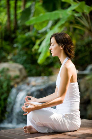 A young woman practising yoga outside Stock Photo