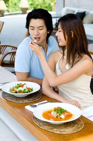 A young Asian couple enjoying lunch oudoors