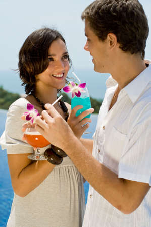 A young couple enjoying drinks on holiday by the pool photo