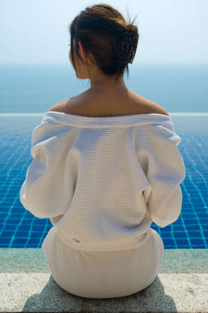A young woman in a robe looking at her pool and sea view photo
