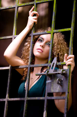 prison bars: A pretty young woman behind bars
