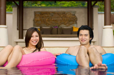 A young couple sitting in rubber rings in swimming pool Stock Photo - 2926368