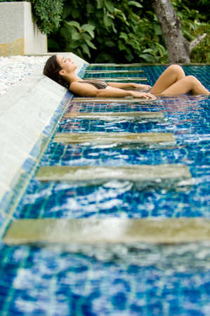 A young woman relaxing in a swimming pool on vacation Stock Photo