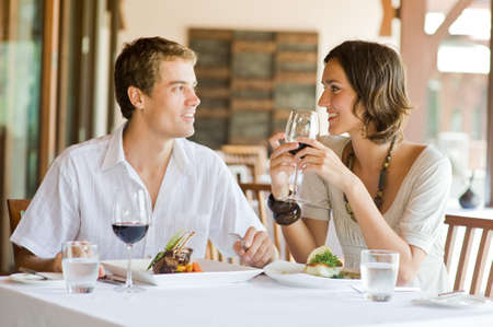 outdoor restaurant: A young couple sitting at a table at an outdoor restaurant Stock Photo