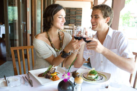 A young couple sitting together in a restaurant holding hands Stock Photo - 2926409