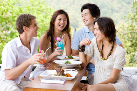 dining: Four young adults enjoying a meal together on vacation Stock Photo