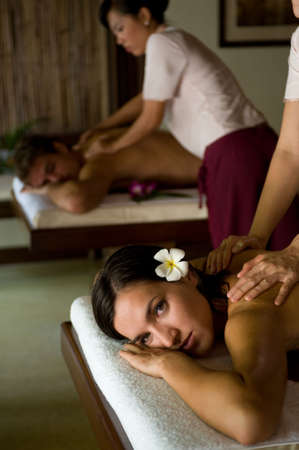A young couple receiving massage treatments together