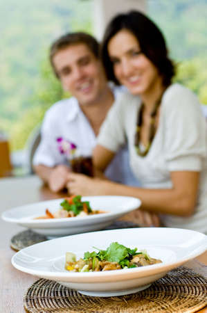 A young couple on vacation eating lunch at a relaxed outdoor restaurant (focus on food) Stock Photo