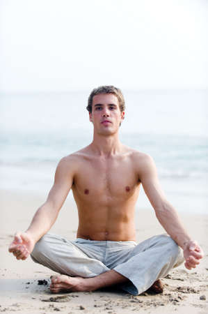 man meditating: A young man in a relaxed sitting position on the beach with ocean behind Stock Photo