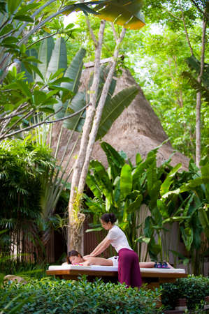 A young woman having massage outside in tropical garden Stock Photo