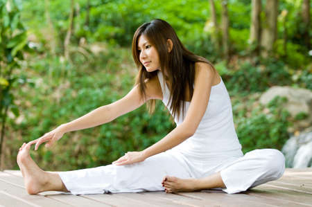 A young woman doing yoga outside in natural environment
