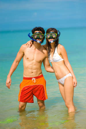 snorkelling: A young couple with snorkelling gear on a tropical beach