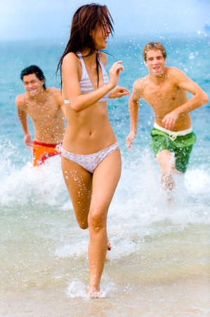 splashed: A young woman is being splashed at the beach by two male friends