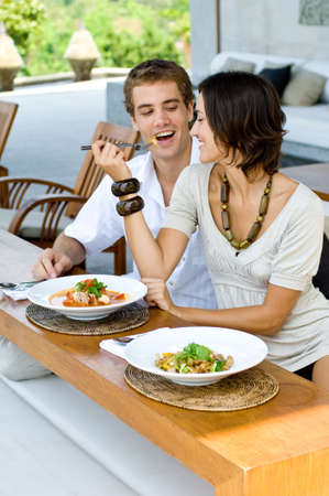alfresco: A young couple on vacation eating lunch at a relaxed outdoor restaurant