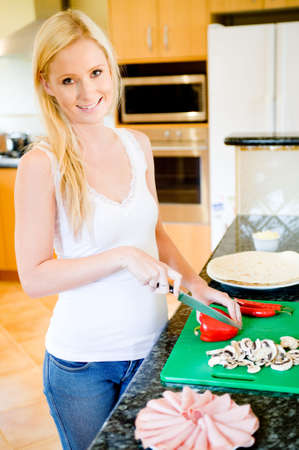A young attractive woman in the kitchen making pizza photo