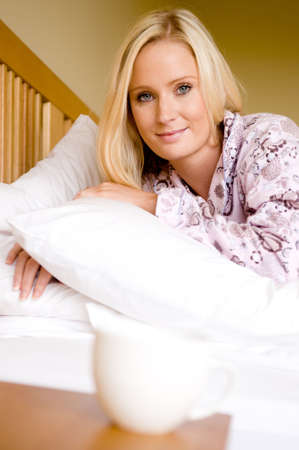 A young woman in pyjamas in bed reaching for morning coffee photo