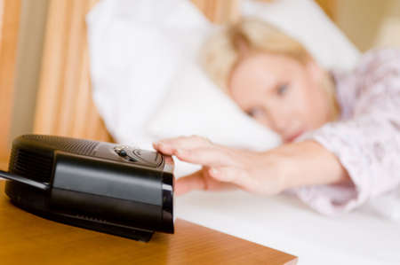 A young attractive woman in bed reaching for snooze button Stock Photo - 3133628