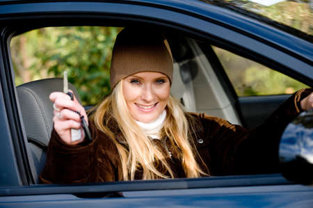 drivers seat: A young woman sitting in drivers seat of a saloon car holding up the keys