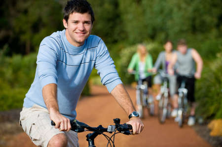 A young man on a bike with group of friends in background