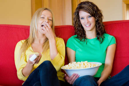 Two young women eating popcorn at home on the sofa and laughing photo