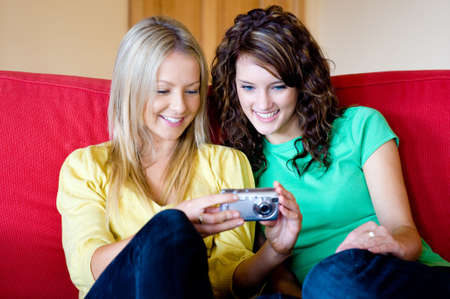 Two young women at home on the sofa with a digital camera photo