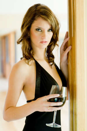 A beautiful young woman in black dress holding glass of red wine photo
