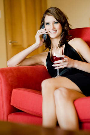 A beautiful young woman in black dress sitting on sofa with phone and wine Stock Photo - 3180041
