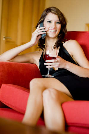 A beautiful young woman in black dress sitting on sofa with phone and wine photo