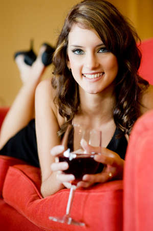 A beautiful young woman in black dress lying on sofa with a glass of wine Stock Photo - 3180034