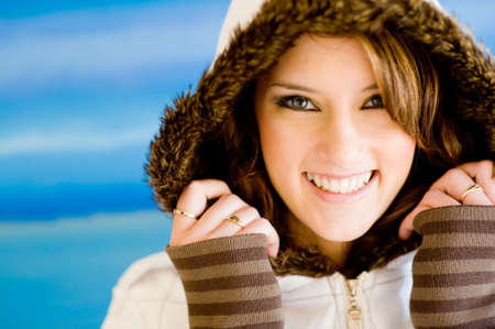 A beautiful young woman in fur-lined coat on blue background Stock Photo