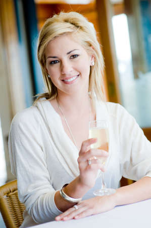 A young attractive woman drinking champagne in a restaurant photo