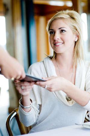 pagando: Una joven mujer atractiva para pagar el almuerzo en un restaurante