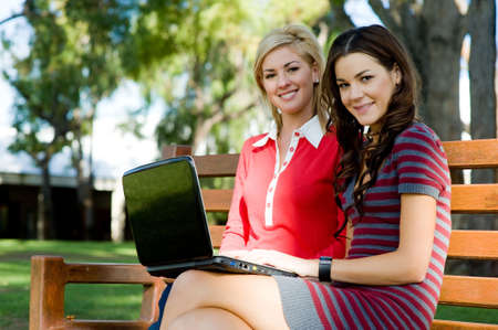 Two young attractive women studying together at college photo