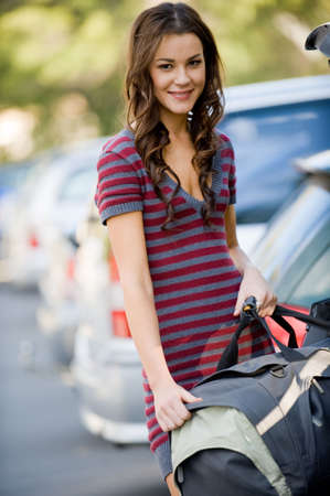 A young female student putting large bag into the car photo