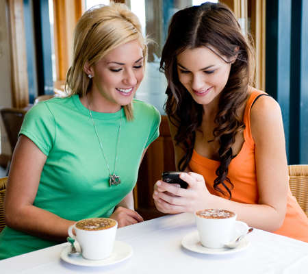 Two young attractive women drinking coffee at a restaurant and looking at phone Stock Photo