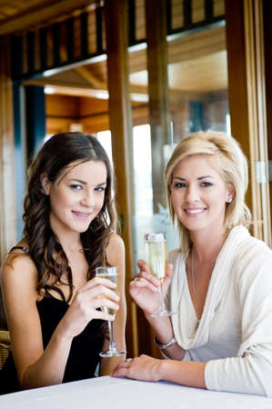 Two young attractive women drinking champagne at a restaurant photo