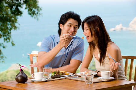outdoor eating: A young couple enjoying breakfast together on vacation Stock Photo