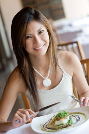 A young woman having dinner at a restaurant Stock Photo